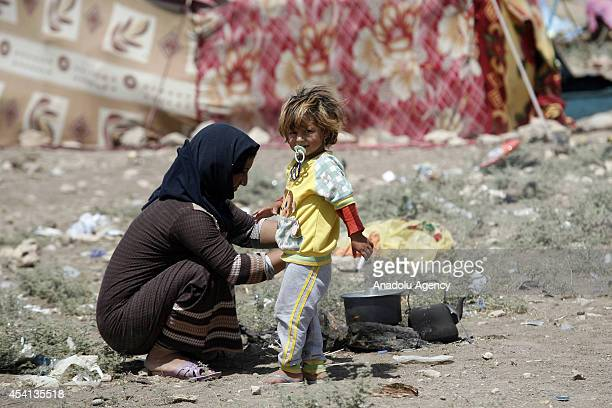 Yezidi woman tries to cook the meal in Zakho district a few kilometers from the IraqiTurkish border Dohuk on August 25 2014 Yezidis fled their home...