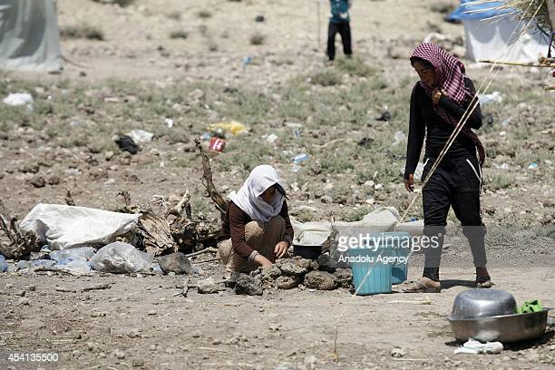 Yezidi women try to cook the meal in Zakho district a few kilometers from the IraqiTurkish border Dohuk on August 25 2014 Yezidis fled their home due...