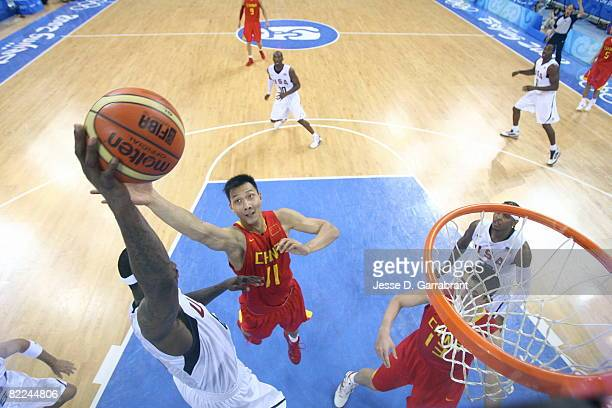 Yi Jianlian of China looks to rebound against LeBron James of the US Men's Senior National Team during day 2 of the men's preliminary basketball game...