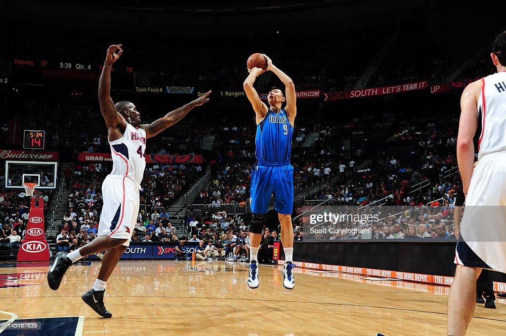 Yi Jianlian of the Dallas Mavericks shoots against Ivan Johnson of the Atlanta Hawks on April 26 2012 at Philips Arena in Atlanta Georgia NOTE TO...