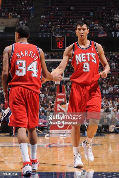 Yi Jianlian of the New Jersey Nets celebrates a play with teammate Devin Harris during the game against the Golden State Warriors on November 1 2008...