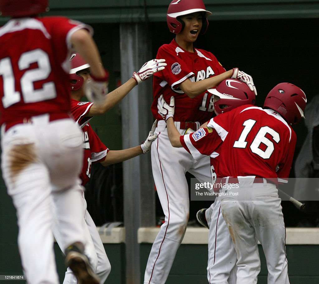 Yi-An Pan (18) celebrates with Colby Ring (6) and Nick Atkinson (16) after Ring scored the winning run for Canada in the bottom of the sixth inning in the first round of the Little League World Series in South Williamsport, Pa., on Friday, August 19, 2011. Ring scored from third on a wild pitch to win the game 6-5 over Middle East/Africa. Photo by Tim Ball/The Washington Post via Getty Images