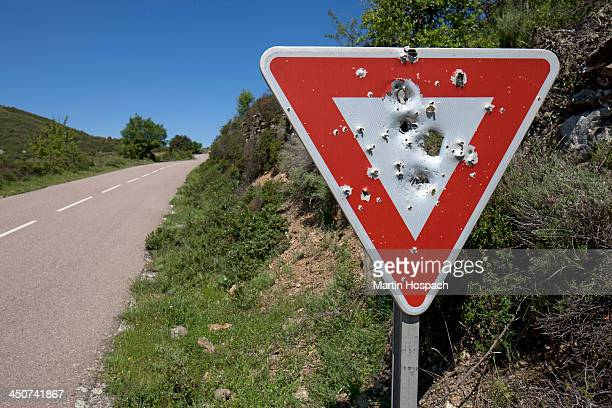 A yield sign with bullet holes in it posted on a remote highway