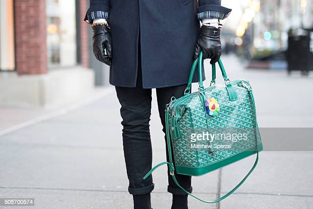 Yihang Yin is seen on Oak Street wearing Vedi Vero glasses navy blue Thom Browne coat green patterned patent leather Goyard bag black Saint Velour...