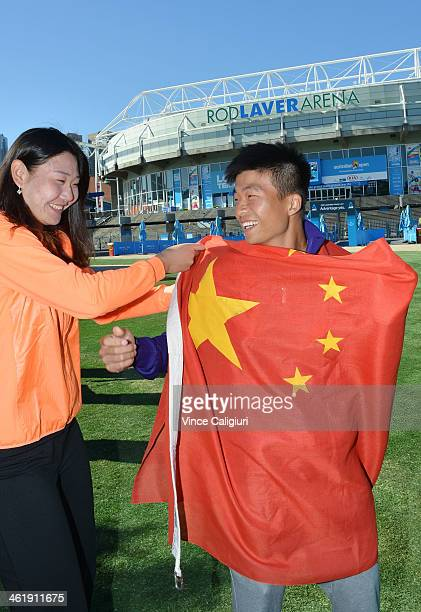 Ying Ying Duan of China helps Di Wu pose with the national flag in front of Rod Laver Arena ahead of the 2014 Australian Open at Melbourne Park on...