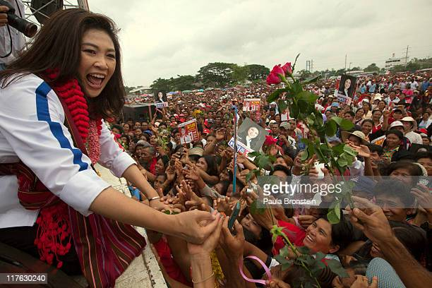 Yingluck Shinawatra reaches out to shakes hands with supporters after speaking at a rally during her election campaign June 29 2011 in Burirum...
