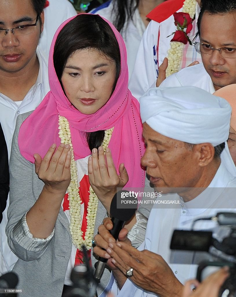 Yingluck Shinawatra, sister of fugitive Thai ex-prime minister Thaksin Shinawatra listens to a Thai-Muslim villager praying for her during the election campaign at a mosque in Bangkok on June 03, 2011. The vote, set for July 3, is shaping up to be a close fight pitting Prime Minister Abhisit Vejjajiva's establishment-backed Democrats against allies of fugitive former premier Thaksin Shinawatra, who was ousted in a 2006 coup.