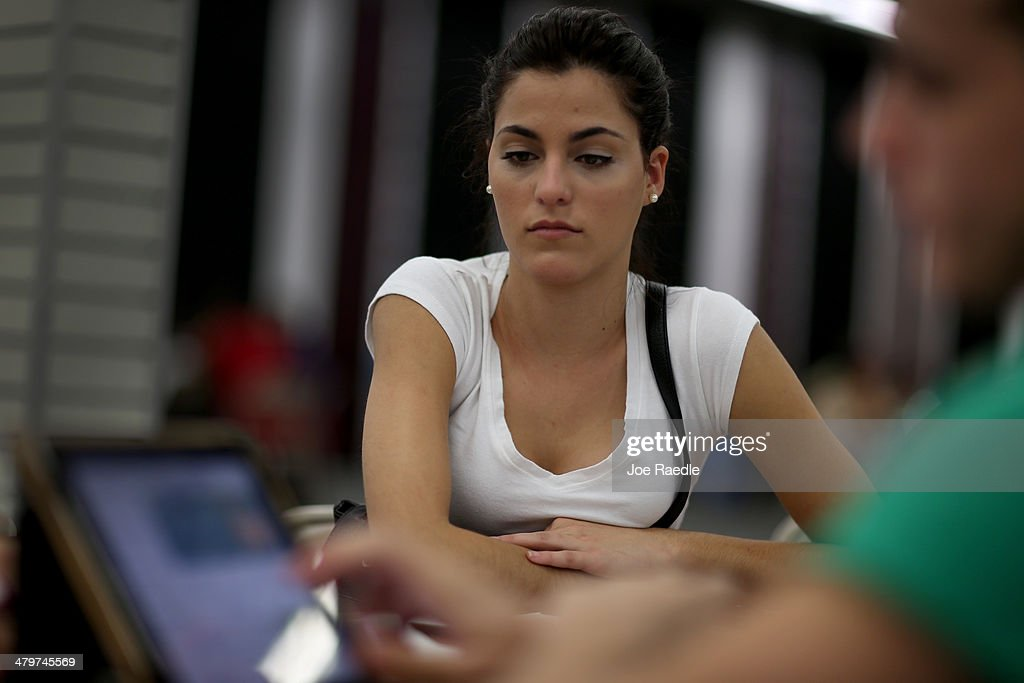 Yislaine Diaz sits with Amaury Garcia an insurance agent from Sunshine Life and Health Advisors as she purchases an individual health insurance policy under the Affordable Care Act at a store setup in the Mall of Americas on March 20, 2014 in Miami, Florida. The owner of Sunshine Life and Health Advisors, Odalys Arevalo, said she has seen a surge in people, some waiting up to 3 hours or more in line, trying to sign up for the Affordable Care Act before the open enrollment period for individual insurance ends on March 31.