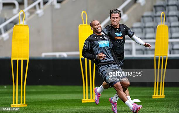 Yoan Gouffran laughs after beating Daryl Janmaat in a race during a Newcastle United Training Session at StJames Park on August 29 in Newcastle upon...