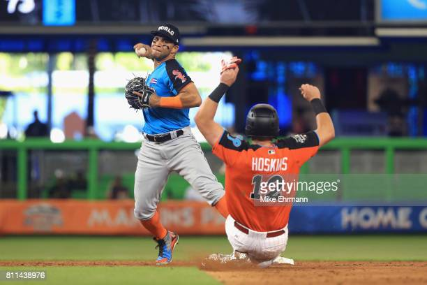 Yoan Moncada of the Chicago White Sox and the World Team attempts to turn a double play on Rhys Hoskins of the Philadelphia Phillies and the US Team...