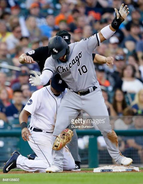 Yoan Moncada of the Chicago White Sox stays on the bag after beating the tag from third baseman Jeimer Candelario of the Detroit Tigers advancing...