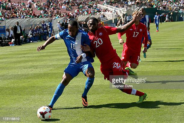 Yoann Arquin of Martinique battles for the ball with Doneil Henry of Canada during the first round of the 2013 CONCACAF Gold Cup at the Rose Bowl on...