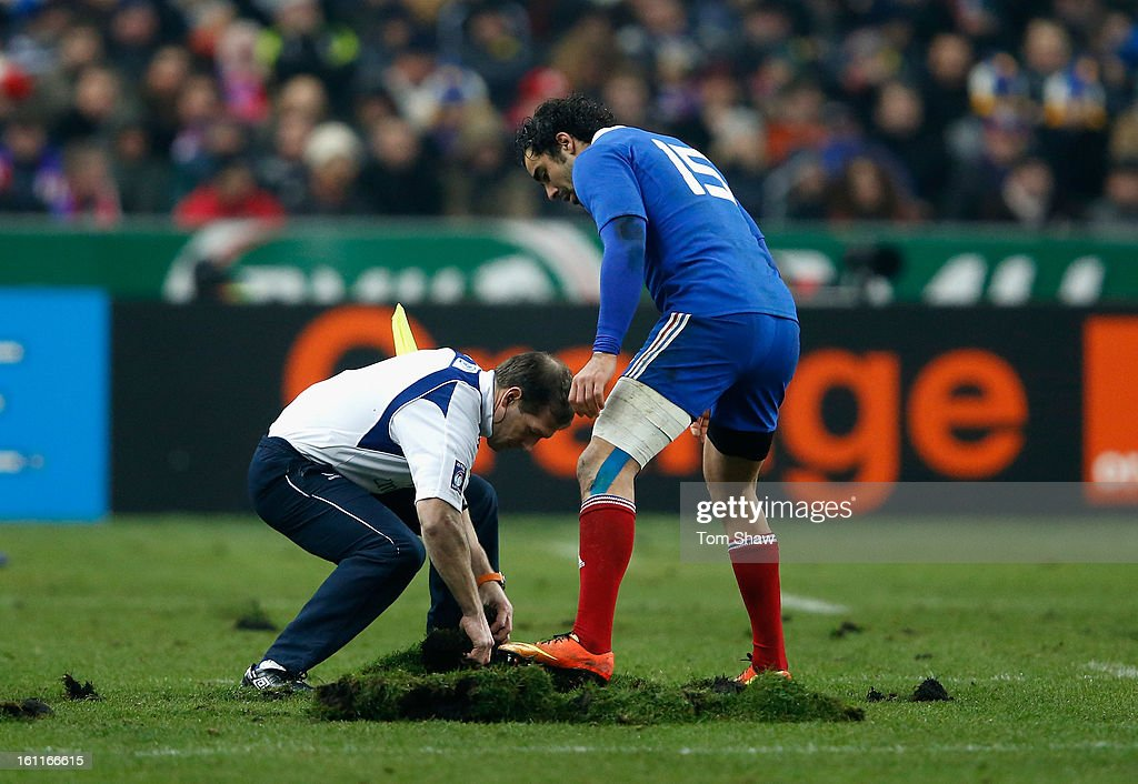 Yoann Huget of France and an official try to repair the pitch during the RBS Six Nations match between France and Wales at Stade de France on February 9, 2013 in Paris, France.