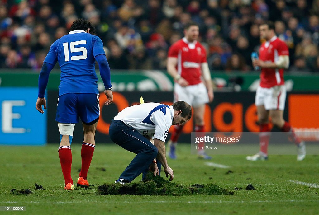 Yoann Huget (L) of France and an official try to repair the pitch during the RBS Six Nations match between France and Wales at Stade de France on February 9, 2013 in Paris, France.