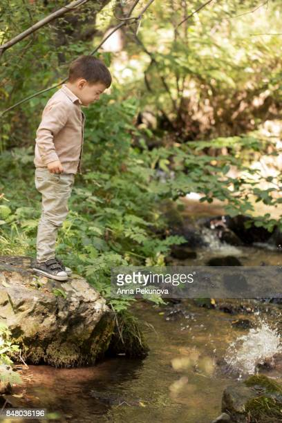 Yoddler boy looking at splashing caused by a thrown stone