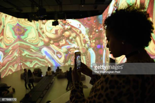 Yodit Gebreyes takes photographs with her smartphone at Artechouse a combination of art and technology artwork projected on the walls and floor of a...