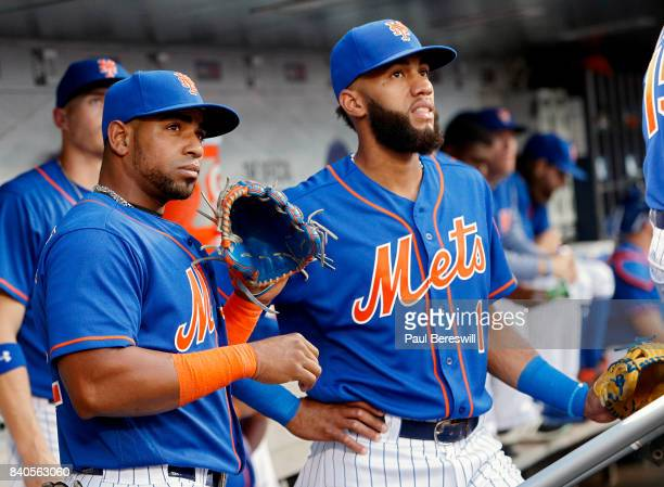Yoenis Cespedes and Amed Rosario of the New York Mets wait to go onto the field in the first inning in an MLB baseball game against the Miami Marlins...