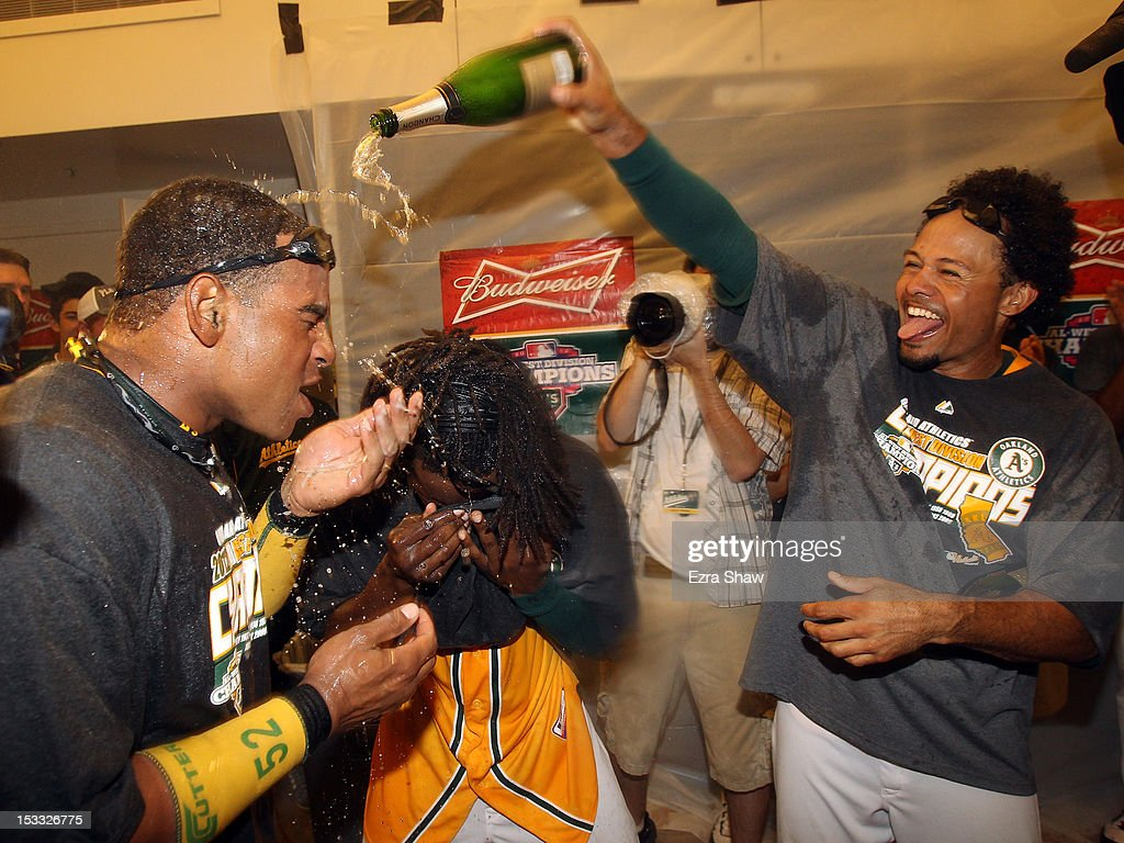 Yoenis Cespedes #52 (L) and Coco Crisp #4 of the Oakland Athletics celebrate in the lockerroom after they beat the Texas Rangers at O.co Coliseum on October 3, 2012 in Oakland, California.