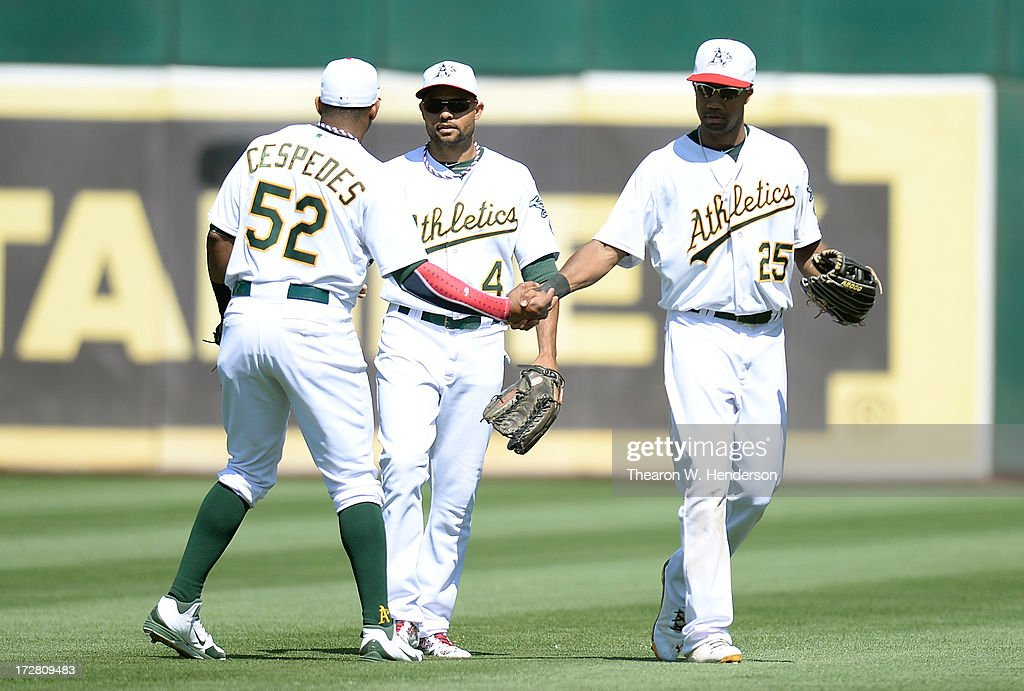 Yoenis Cespedes #52, Coco Crisp #4 and Chris Young #25 of the Oakland Athletics celebrate defeating the Chicago Cubs 1-0 at O.co Coliseum on July 4, 2013 in Oakland, California.
