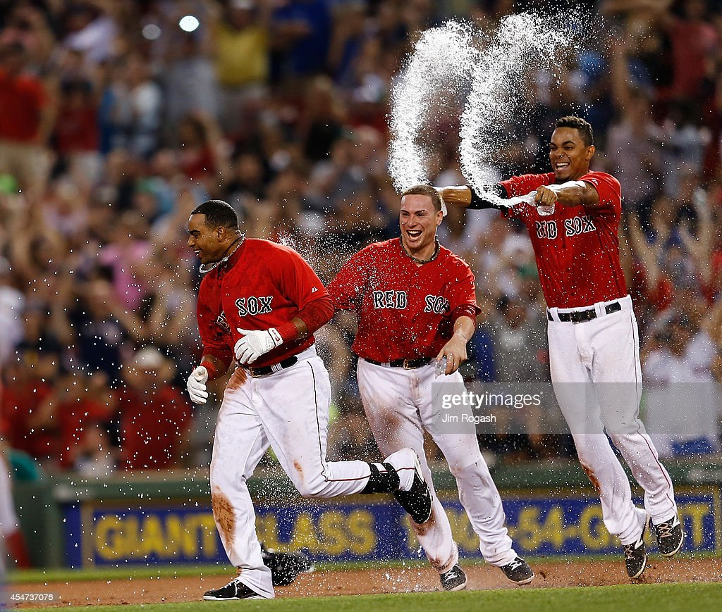 Yoenis Cespedes #52 of the Boston Red Sox celebrates with teammates Christian Vazquez and Xander Bogaerts #2 of the Boston Red Sox after knocking in the winning run in the 10th inning with a double at Fenway Park on September 5, 2014 in Boston, Massachusetts.