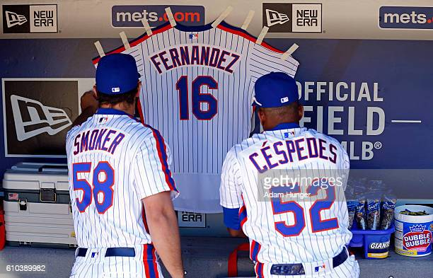 Yoenis Cespedes of the New York Mets and Josh Smoker of the New York Mets hang a jersey for Jose Fernandez of the Miami Marlins in their dugout prior...