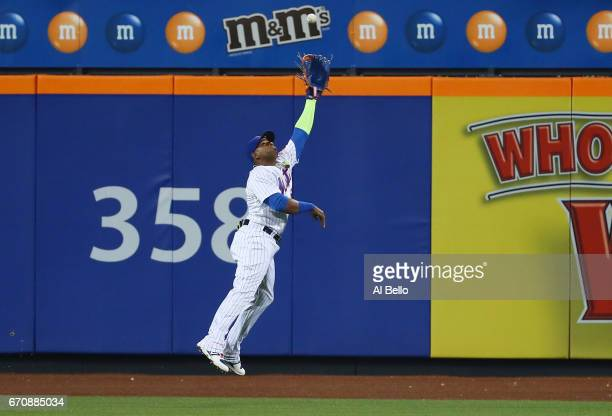 Yoenis Cespedes of the New York Mets cannot reach a ball hits a by Maikel Franco of the Philadelphia Phillies resulting in a double and a run scored...