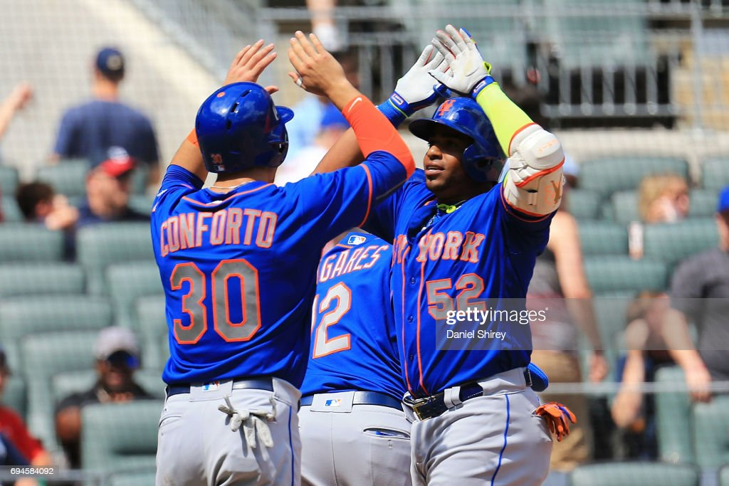 Yoenis Cespedes #52 of the New York Mets celebrates a grand slam with Michael Conforto #30 during the ninth inning against the Atlanta Braves at SunTrust Park on June 10, 2017 in Atlanta, Georgia.