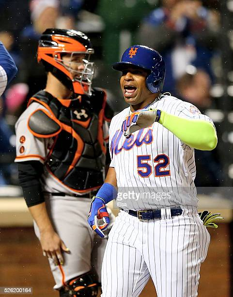 Yoenis Cespedes of the New York Mets celebrates his grand slam in the third inning as Buster Posey of the San Francisco Giants looks on at Citi Field...