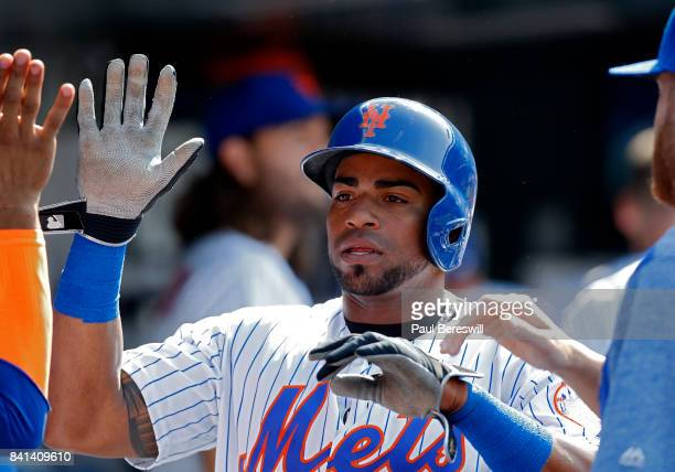 Yoenis Cespedes of the New York Mets celebrates in the dugout after scoring a run in an MLB baseball game against the Miami Marlins on August 20 2017...