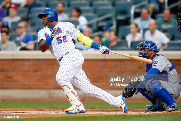 Yoenis Cespedes of the New York Mets follows through on a first inning single against the Chicago Cubs at Citi Field on June 12 2017 in the Flushing...