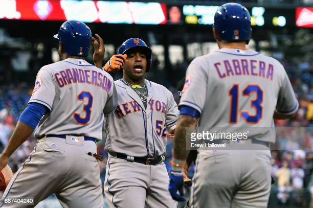 Yoenis Cespedes of the New York Mets is congratulated by teammates Curtis Granderson and Asdrubal Cabrera after hitting a three run home run in the...