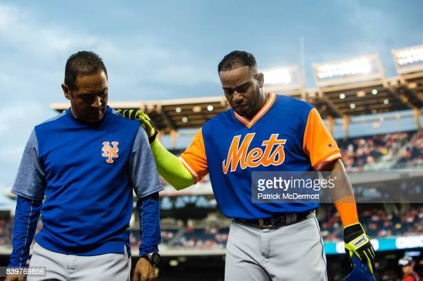Yoenis Cespedes of the New York Mets is helped off the field by Mets head athletic trainer Ray Ramirez after an apparent leg injury in the first...