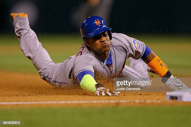 Yoenis Cespedes of the New York Mets slides into third with a stolen base during the eighth inning against the Colorado Rockies at Coors Field on...