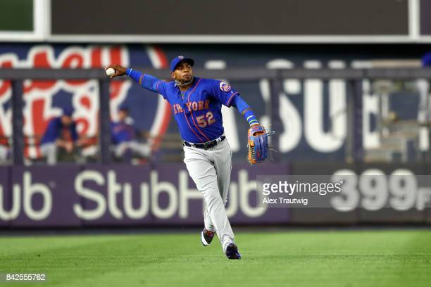 Yoenis Cespedes of the New York Mets throws after making a catch during the game against the New York Yankees at Yankee Stadium on Monday August 14...