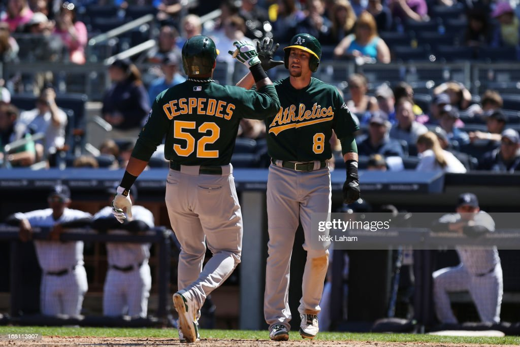 Yoenis Cespedes #52 of the Oakland Athletics celebrates his two RBI home run with scoring run Jed Lowrie #8 against the New York Yankees at Yankee Stadium on May 5, 2013 in the Bronx borough of New York City.