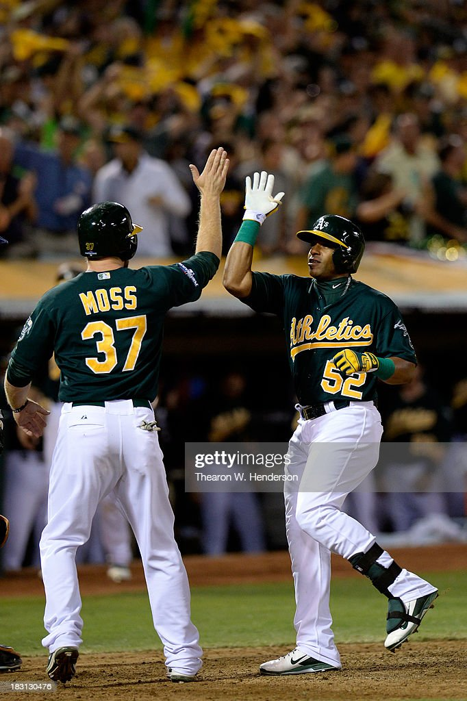 Yoenis Cespedes #52 of the Oakland Athletics celebrates with teammate Brandon Moss #37 after hitting a two run home run in the seventh inning against Max Scherzer #37 of the Detroit Tigers during Game One of the American League Division Series at O.co Coliseum on October 4, 2013 in Oakland, California.