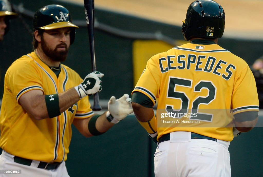 Yoenis Cespedes #52 of the Oakland Athletics is congratulated by <a gi-track='captionPersonalityLinkClicked' href=/galleries/search?phrase=Derek+Norris&family=editorial&specificpeople=6795804 ng-click='$event.stopPropagation()'>Derek Norris</a> #36 after Cespedes scored during the second inning against the San Francisco Giants at O.co Coliseum on May 28, 2013 in Oakland, California.