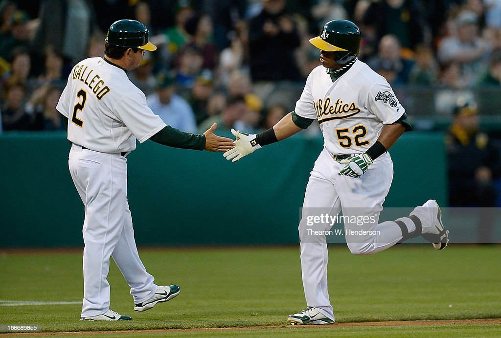 <a gi-track='captionPersonalityLinkClicked' href=/galleries/search?phrase=Yoenis+Cespedes&family=editorial&specificpeople=8892047 ng-click='$event.stopPropagation()'>Yoenis Cespedes</a> #52 of the Oakland Athletics is congratulated by third base coach <a gi-track='captionPersonalityLinkClicked' href=/galleries/search?phrase=Mike+Gallego&family=editorial&specificpeople=836149 ng-click='$event.stopPropagation()'>Mike Gallego</a> #2 after Cespedes hit a solo home run against the Texas Rangers in the third inning at O.co Coliseum on May 13, 2013 in Oakland, California.