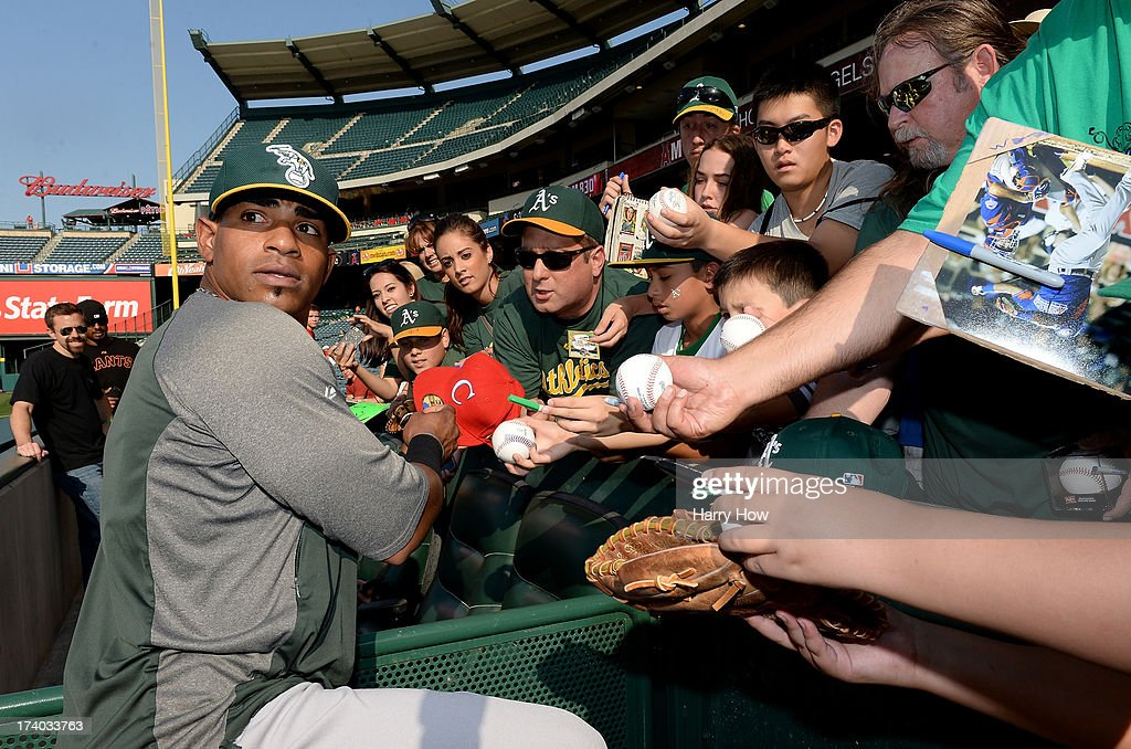 Yoenis Cespedes #52 of the Oakland Athletics looks back to the field as he signs autographs for fans prior to the game against the Los Angeles Angels at Angel Stadium of Anaheim on July 19, 2013 in Anaheim, California.