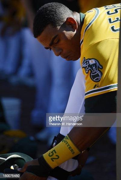 Yoenis Cespedes of the Oakland Athletics puts on his shin guard prepairing to hit against the Los Angeles Angels of Anaheim at Oco Coliseum on August...