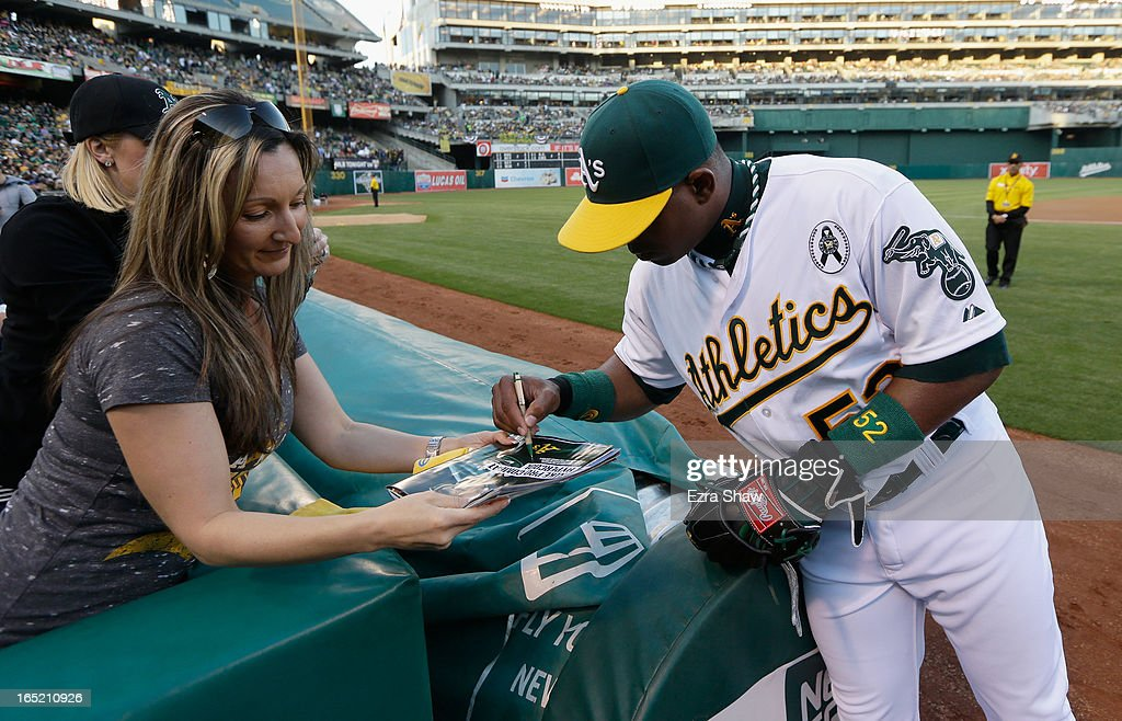 Yoenis Cespedes #52 of the Oakland Athletics signs autographs before their game against the Seattle Mariners during Opening Day at O.co Coliseum on April 1, 2013 in Oakland, California.