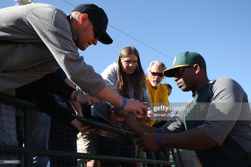 <a gi-track='captionPersonalityLinkClicked' href=/galleries/search?phrase=Yoenis+Cespedes&family=editorial&specificpeople=8892047 ng-click='$event.stopPropagation()'>Yoenis Cespedes</a> #52 of the Oakland Athletics signs autographs during a spring training workout at Phoenix Municipal Stadium on February 28, 2013 in Phoenix, Arizona.