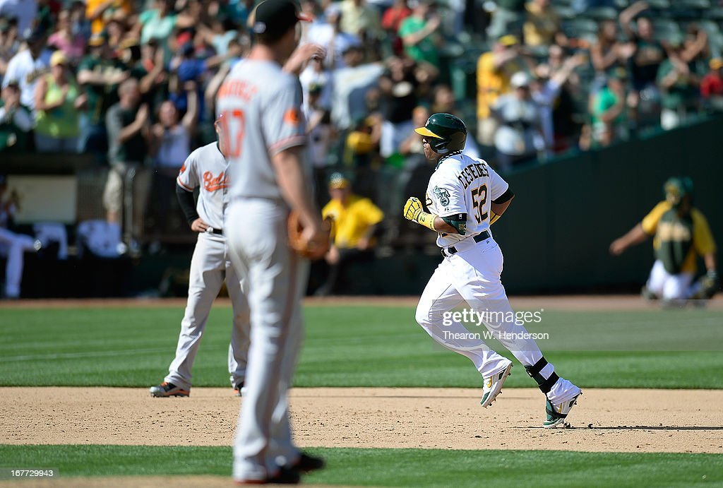 Yoenis Cespedes #52 of the Oakland Athletics trots around the bases after hitting a two-run home run with two out to tie the game 8-8, as pitcher <a gi-track='captionPersonalityLinkClicked' href=/galleries/search?phrase=Brian+Matusz&family=editorial&specificpeople=4412757 ng-click='$event.stopPropagation()'>Brian Matusz</a> #17 of the Baltimore Orioles looks on in the ninth inning at O.co Coliseum on April 28, 2013 in Oakland, California.