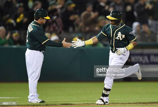 Yoenis Cespedes of the Oakland Athletics trotting around the bases is congratulated by third base coach Mike Gallego after Cespedes hit a solo home...