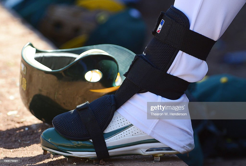 Yoenis Cespedes of the Oakland Athletics wearing Nike baseball cleats and his shin guard stands at the end of the dugout looking on against the Los...