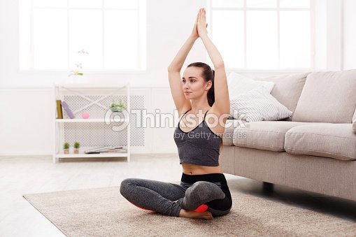 yoga zu hause frau tun lotus pose stock foto thinkstock. Black Bedroom Furniture Sets. Home Design Ideas