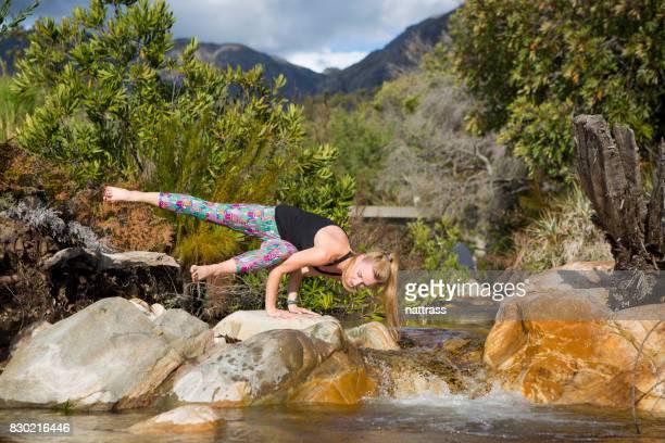 Yoga - équilibre sur un rocher dans la rivière