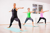 Three girls practicing yoga, Virabhadrasana / Warrior 2 pose