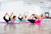 Three girls practicing yoga, Yoga - Dhanurasana/Bow pose