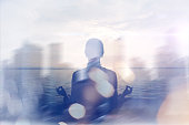 Yoga concept. Double exposure. Woman doing yoga practice on the beach and silhouette of modern city. Blurred effect, lens flare effect, intentional sun glare